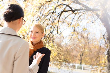 conversing: Businesswomen conversing at park on sunny day