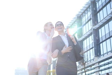 personas hablando: Feliz de negocios que susurra en el edificio de oficinas fuera de la oreja de su colega en el d�a soleado