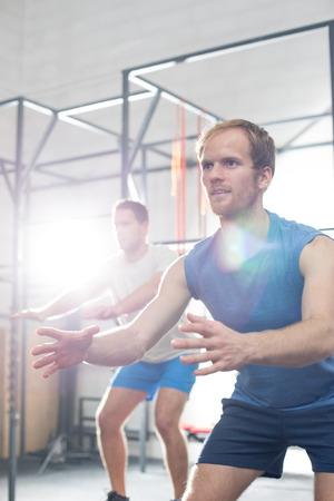 men exercising: hombres decididos que ejercen en el gimnasio de crossfit