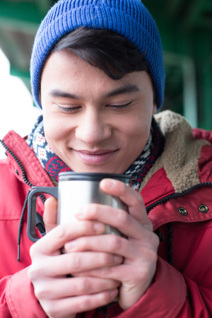 insulated drink container: Smiling man looking at coffee in insulated drink container during winter LANG_EVOIMAGES