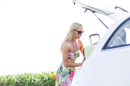 ���clear sky���: Female friends loading luggage in car trunk against clear sky