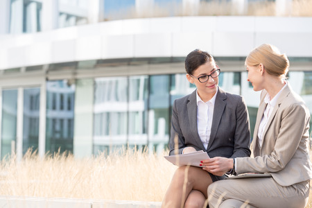 office attire: Businesswomen discussing over documents while sitting outside office building