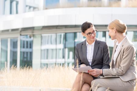 papeles oficina: Empresarias que discuten sobre los documentos mientras se est� sentado fuera de edificio de oficinas