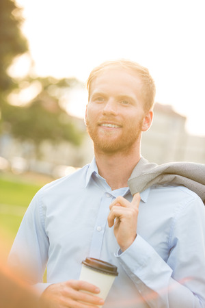 disposable cup: Happy businessman holding disposable cup outdoors