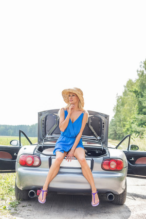 ���clear sky���: Thoughtful woman sitting on convertible trunk against clear sky
