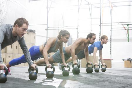 muscle training: Engagierte Menschen tun Liegest�tze mit den Kettlebells bei CrossFit Fitness-Studio