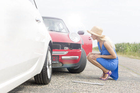 damaged cars: Full-length side view of tensed woman looking at damaged cars on road
