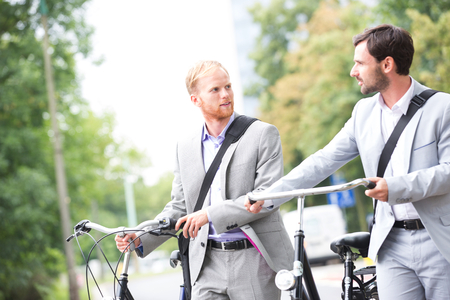transportation: Businessmen looking at each other while holding bicycles outdoors LANG_EVOIMAGES