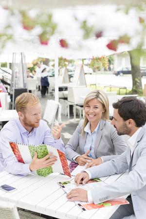 sidewalk talk: Portrait of happy businesswoman with male colleagues deciding menu at sidewalk cafe