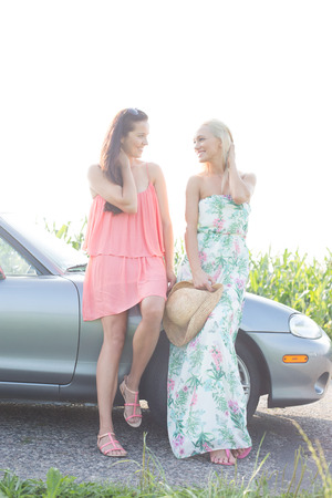 conversing: Happy female friends conversing while standing by convertible against clear sky