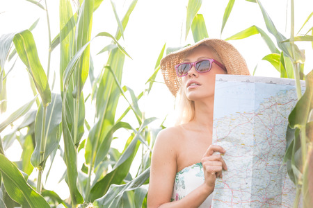 clear away: Woman holding map while standing amidst plants outdoors