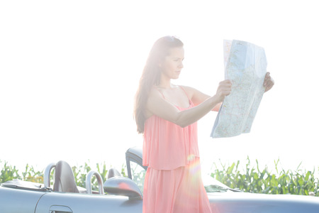 ���clear sky���: Woman reading map while standing by convertible against clear sky LANG_EVOIMAGES