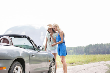 ���clear sky���: Women examining broken down car on sunny day against clear sky LANG_EVOIMAGES