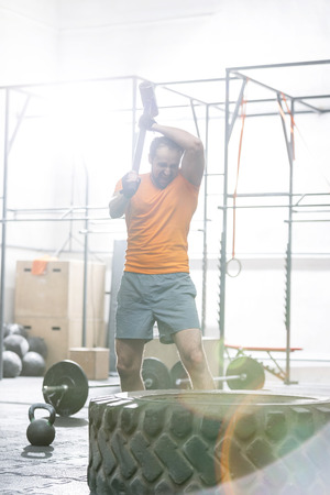 holding aloft: Determined man hitting tire with sledgehammer in crossfit gym