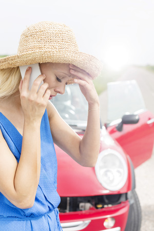 tensed: Tensed young woman using cell phone by broken down car