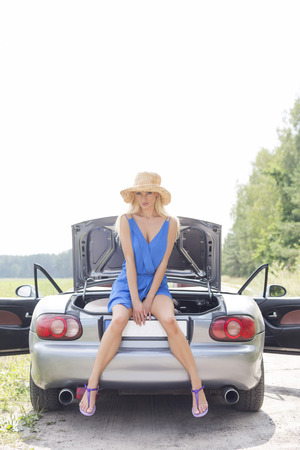 ���clear sky���: Full length portrait of woman sitting on convertible trunk against clear sky