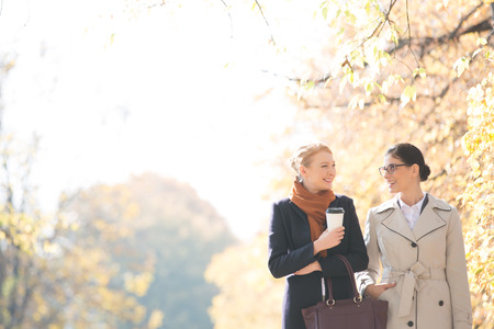 conversation: Happy businesswomen conversing while walking at park on sunny day