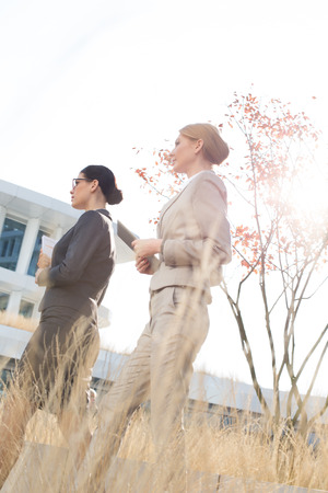 ���clear sky���: Side view of confident businesswomen walking against clear sky