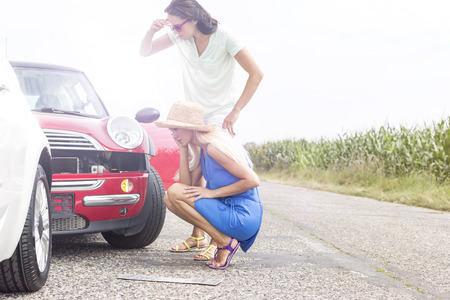 damaged cars: Tensed women looking at damaged cars on road against clear sky