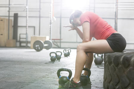 Exhausted woman sitting on tire in crossfit gym LANG_EVOIMAGES