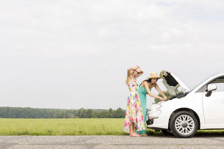 broken down: Friends examining broken down car on country road against clear sky