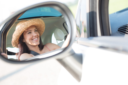 rearview: Reflection of happy woman in rearview mirror of car LANG_EVOIMAGES