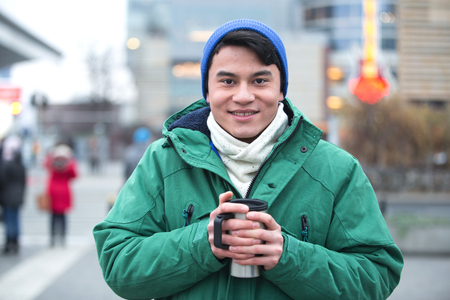 incidental people: Portrait of man in winter clothing smiling on city street