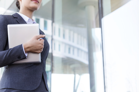 midsection: Midsection of businesswoman holding tablet PC by glass wall