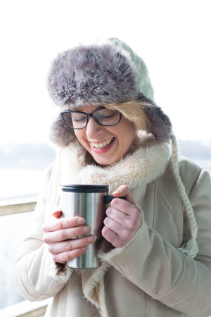 warm clothing: Cheerful woman in warm clothing holding insulated drink container LANG_EVOIMAGES