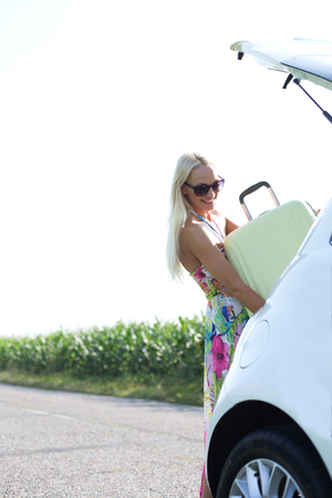 ���clear sky���: Happy woman loading suitcase in car trunk against clear sky LANG_EVOIMAGES