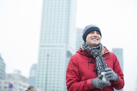 warm clothing: Happy man in warm clothing holding disposable cup outdoors