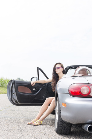 ���clear sky���: Young woman sitting in convertible on country road against clear sky