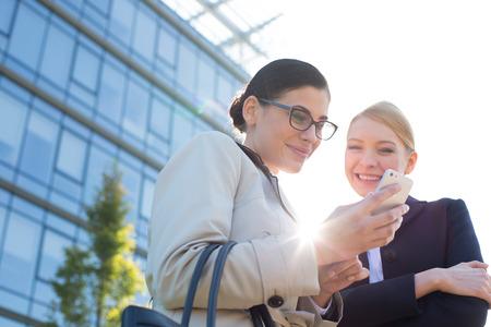 personas de pie: �ngulo de visi�n baja de empresarias feliz con tel�fono inteligente
