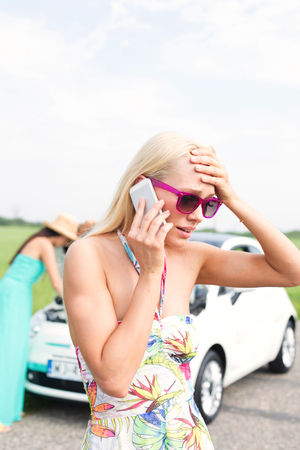 inconvenience: Frustrated woman using cell phone while friend examining broken down car at countryside