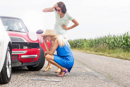 damaged: Tensed women looking at damaged cars on road against clear sky
