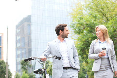 conversing: Businesspeople with bicycle and disposable cup conversing while walking outdoors