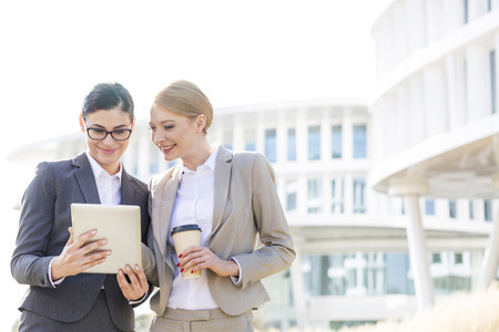 office attire: Happy businesswomen using digital tablet outside office building LANG_EVOIMAGES