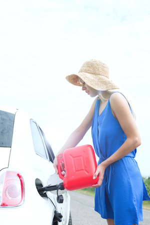 refueling: Side view of woman refueling car on country road LANG_EVOIMAGES
