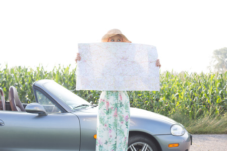 ���clear sky���: Woman hiding face with map by convertible against clear sky