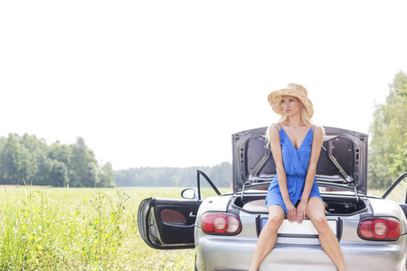 ���clear sky���: Young woman sitting on convertible trunk against clear sky