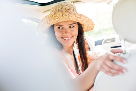 looking back: Happy woman looking back while driving car