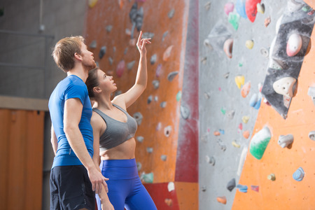 climbing  wall: Man and woman discussing by climbing wall in crossfit gym
