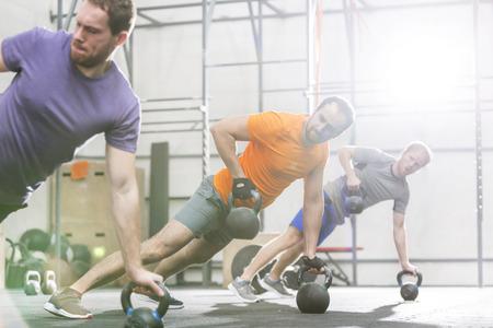 men exercising: Los hombres que ejercitan con pesas en un gimnasio CrossFit