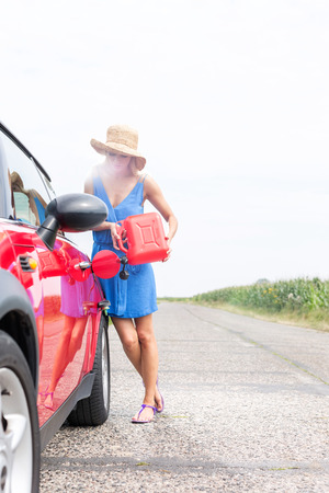 ���clear sky���: Full-length of woman refueling car on country road against clear sky