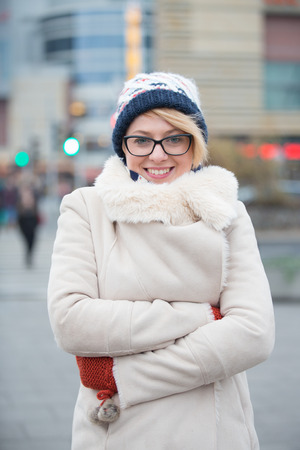 warm clothing: Portrait of happy woman in warm clothing standing arms crossed on city street