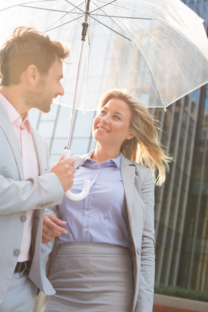 conversing: Happy business couple conversing under umbrella outdoors