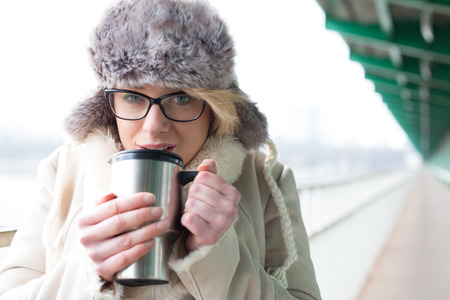 insulated drink container: Portrait of woman drinking coffee from insulated drink container during winter
