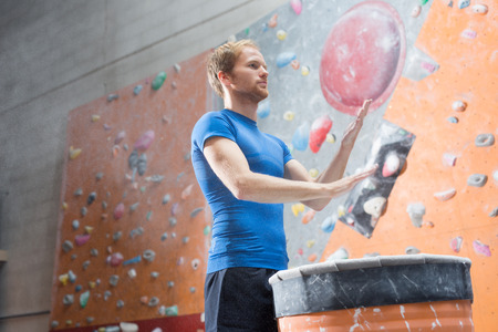 climbing wall: Low angle view of confident man dusting powder by climbing wall in crossfit gym LANG_EVOIMAGES