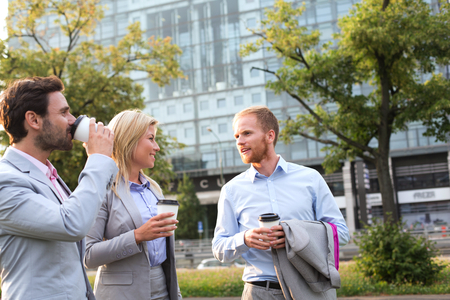 conversing: Businesspeople with disposable cups conversing in city