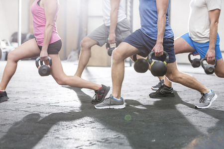physical training: Low section of people lifting kettlebells at crossfit gym